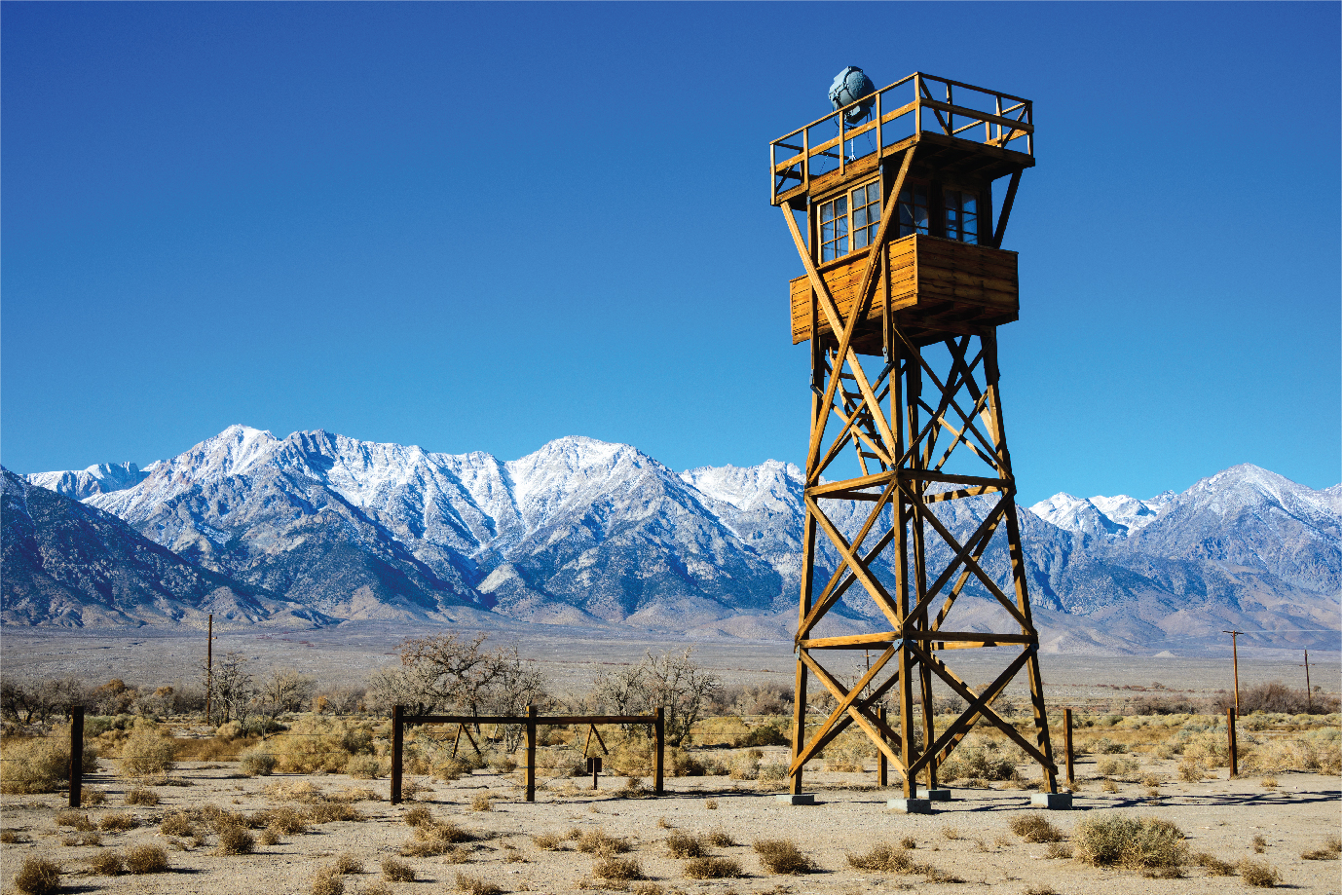 A guard tower on the border of a fenced camp in the desert.