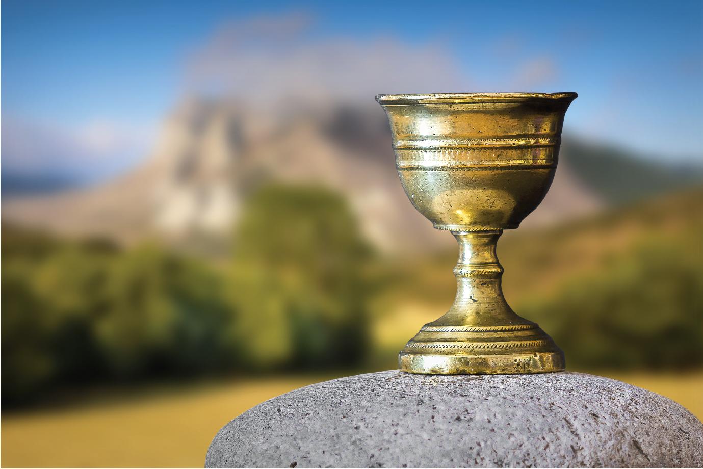 A gold goblet a top a rock