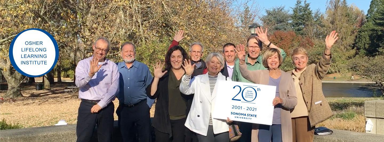 OLLI Cohort holding an OLLI 20th Sign